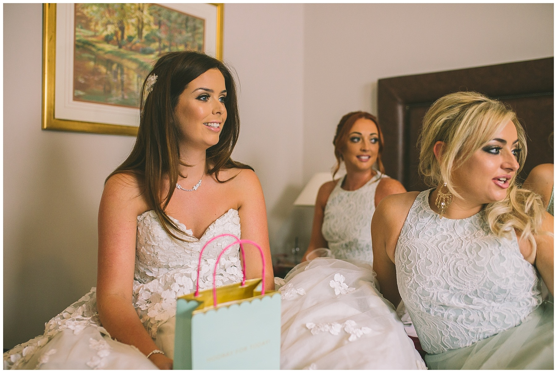 bride and bridesmaids sat on bed ahead of rivington barn wedding