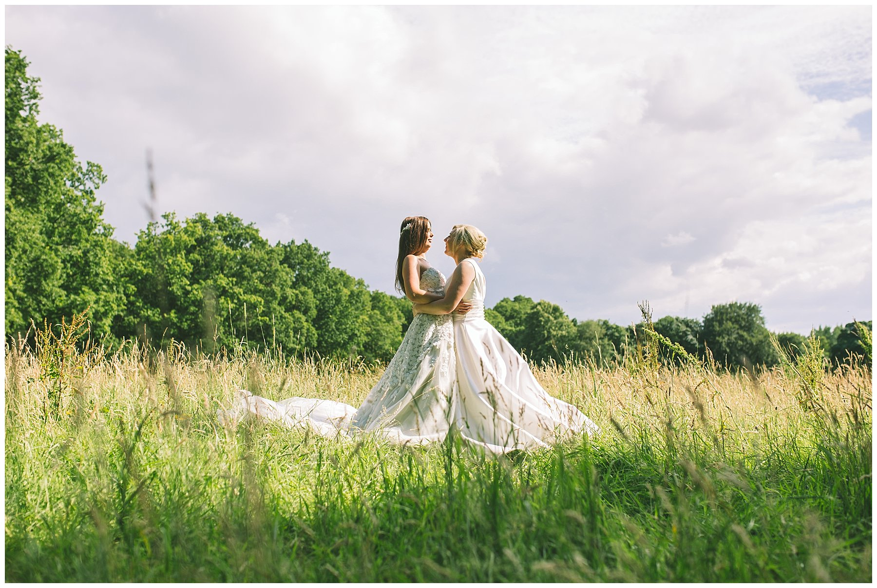 two brides in long grass at wedding venue
