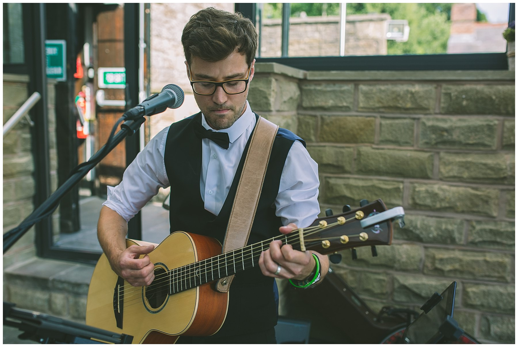 acoustic guitarist entertains wedding guests at rivington barn