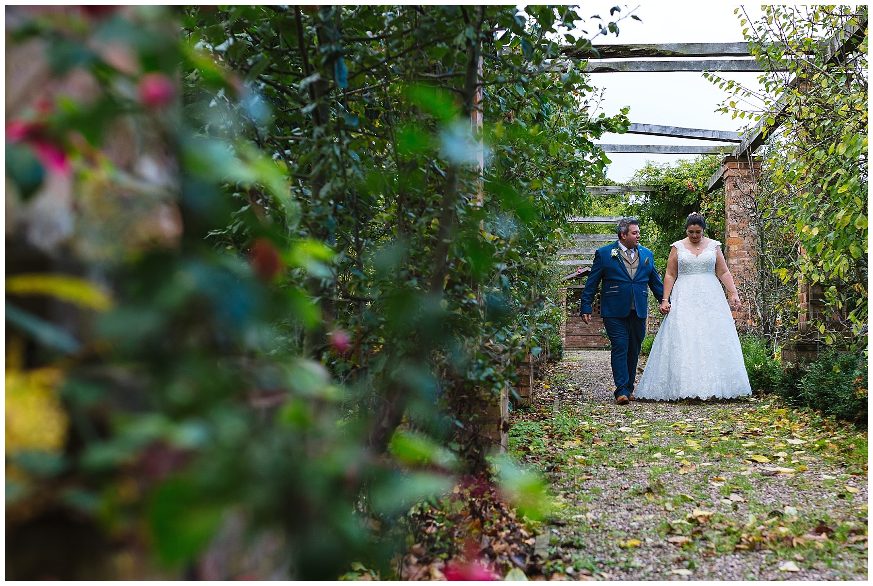 married couple walk through the gardens at willington hall