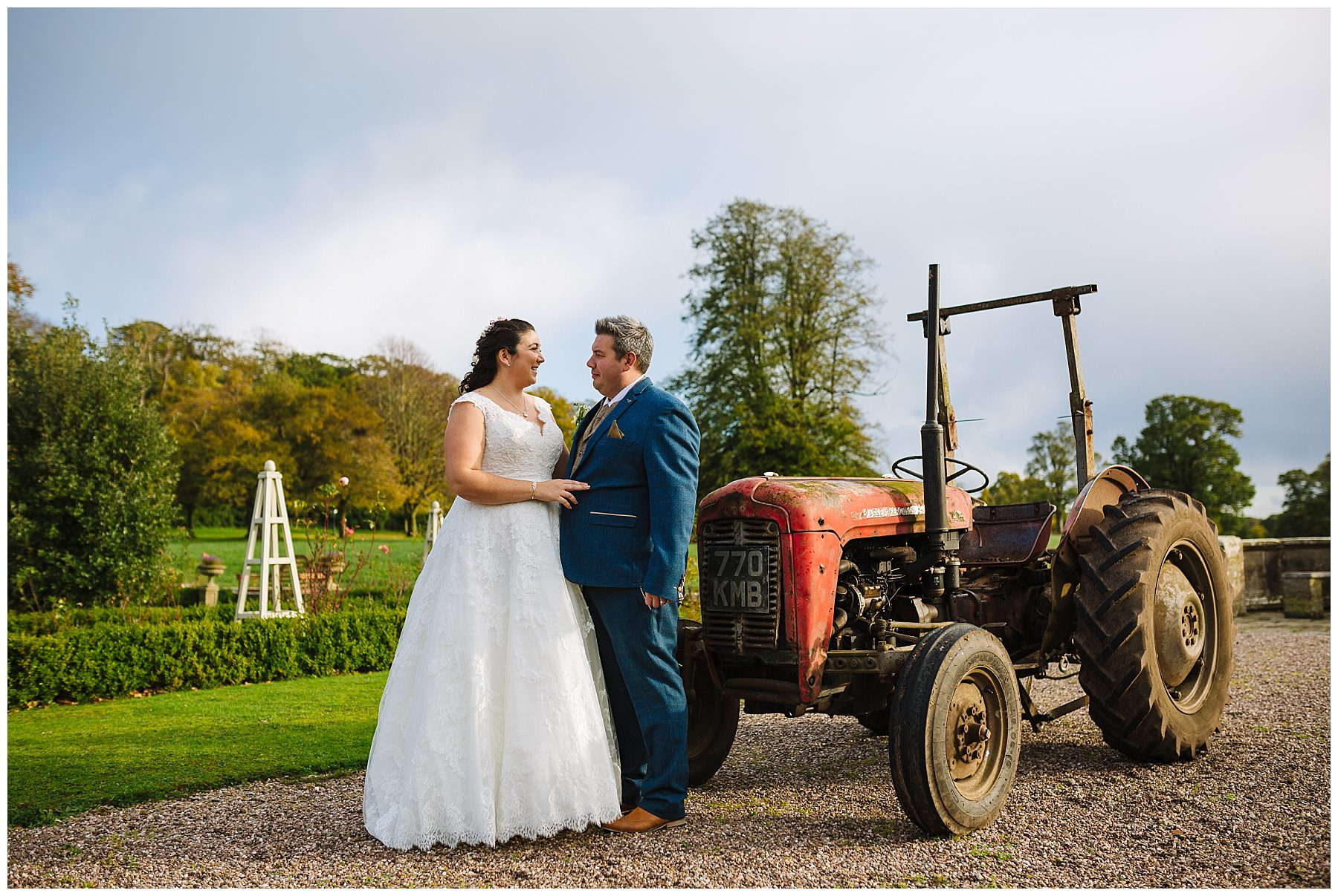 bride and groom stand by tractor at willington hall