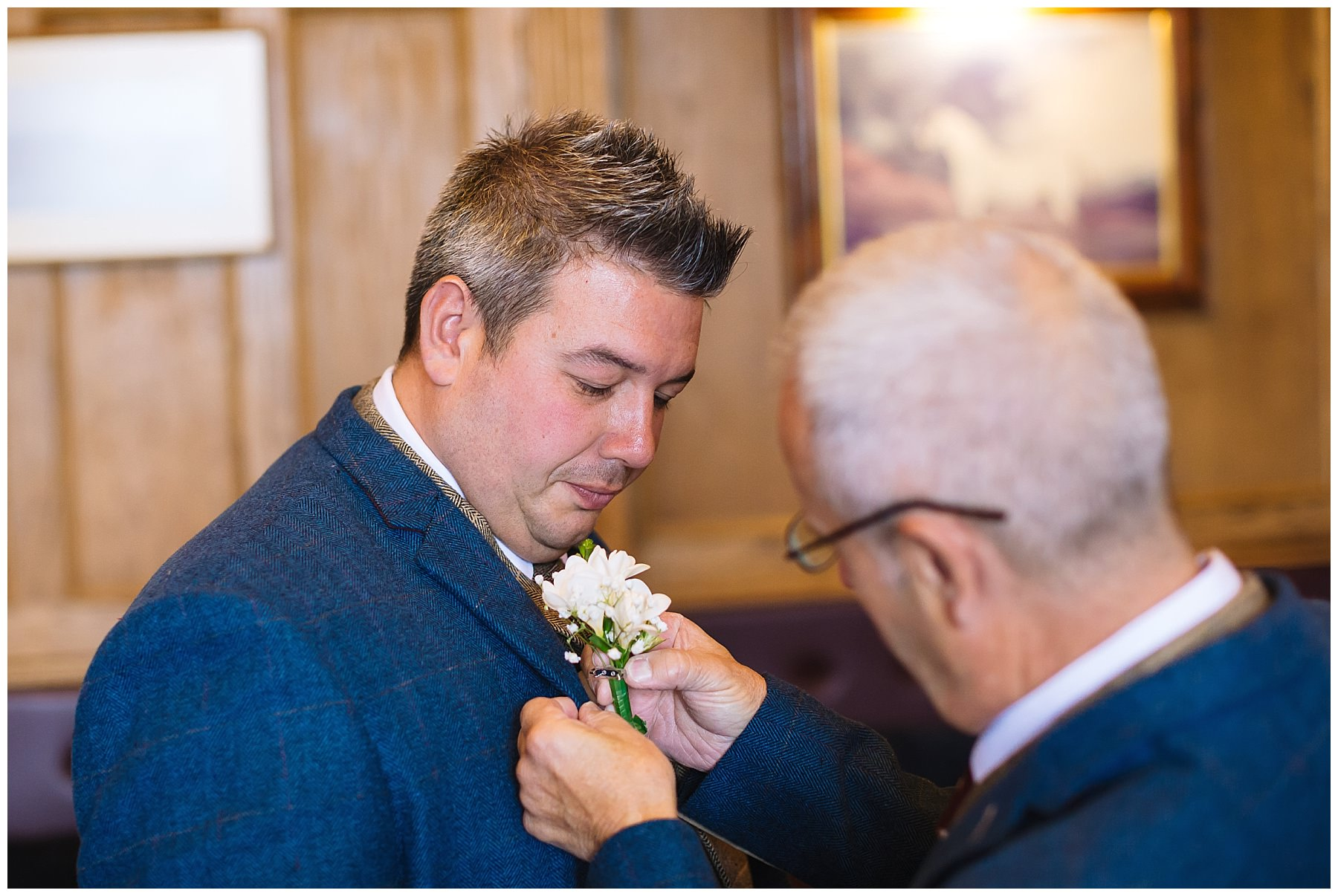 groom has buttonhole fixed by groomsman