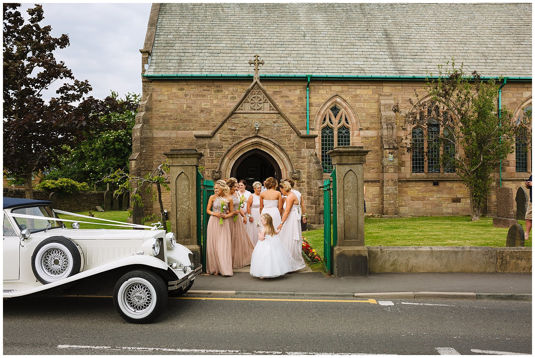 Bridesmaids wait outside church as the bridal car arrives
