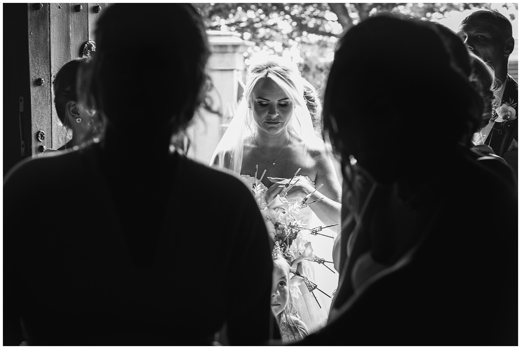 bride in black and white making finishing touches in church doorway