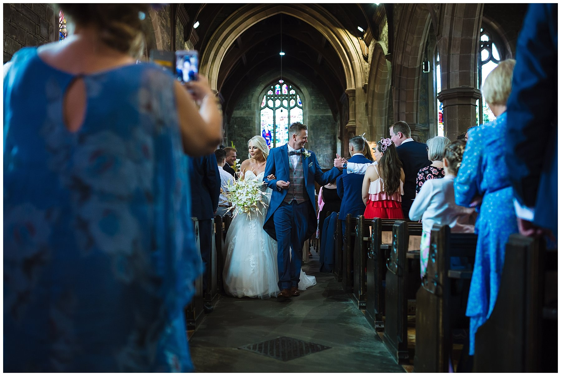 bride and groom exit church to applause