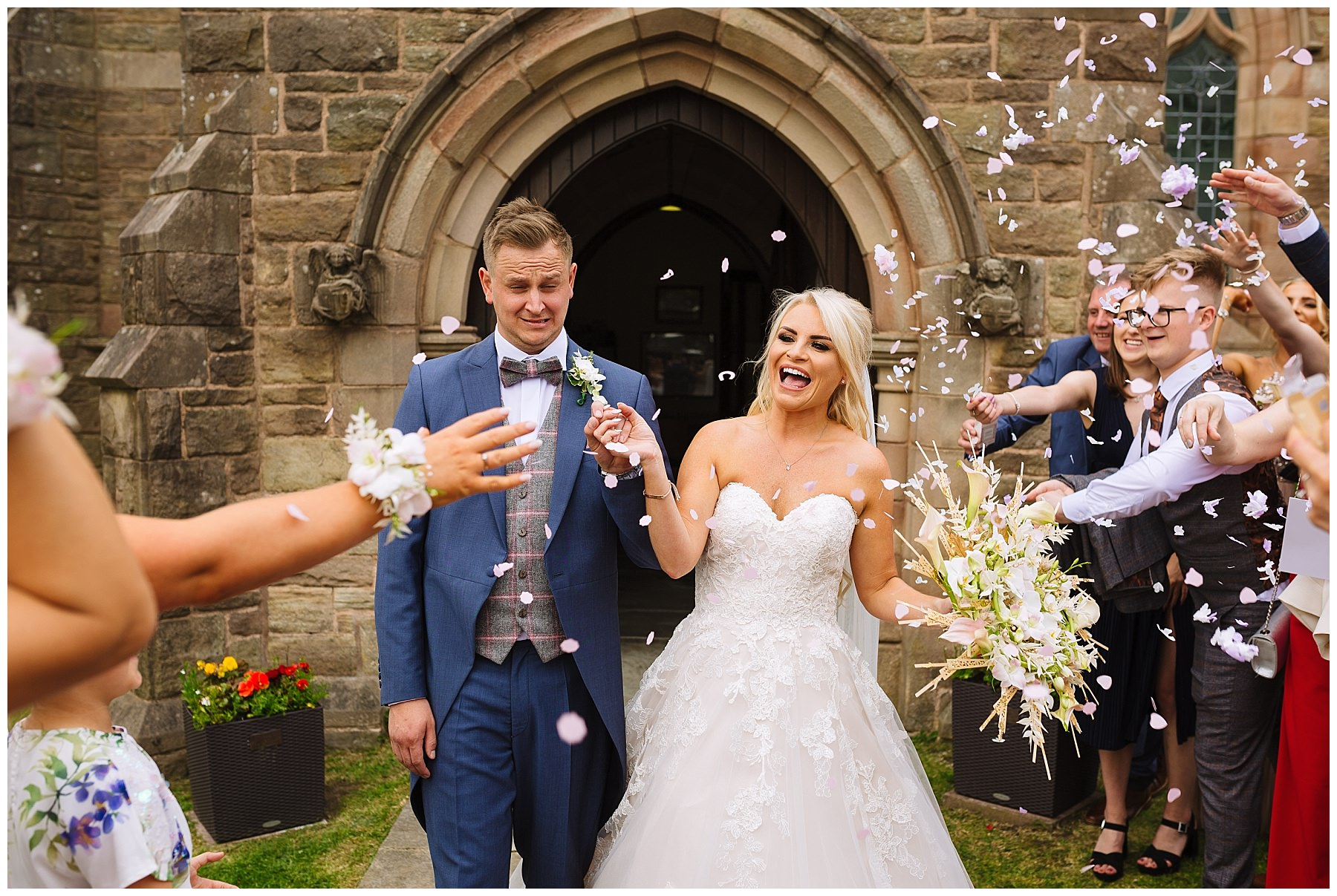 bride and groom laugh as they exit church to a shower of confetti