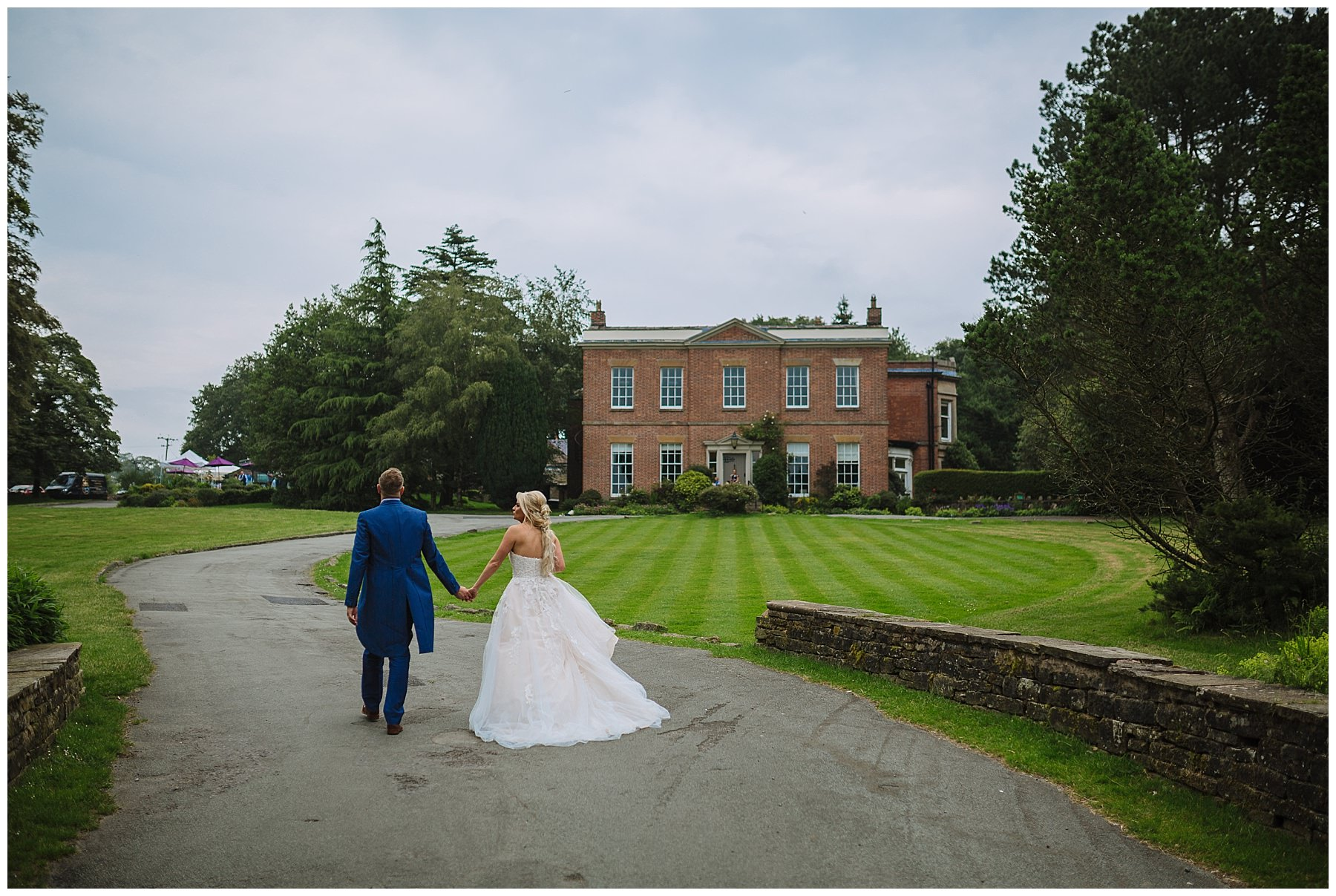 bride and groom walk hand in hand through the grounds at rivington barn