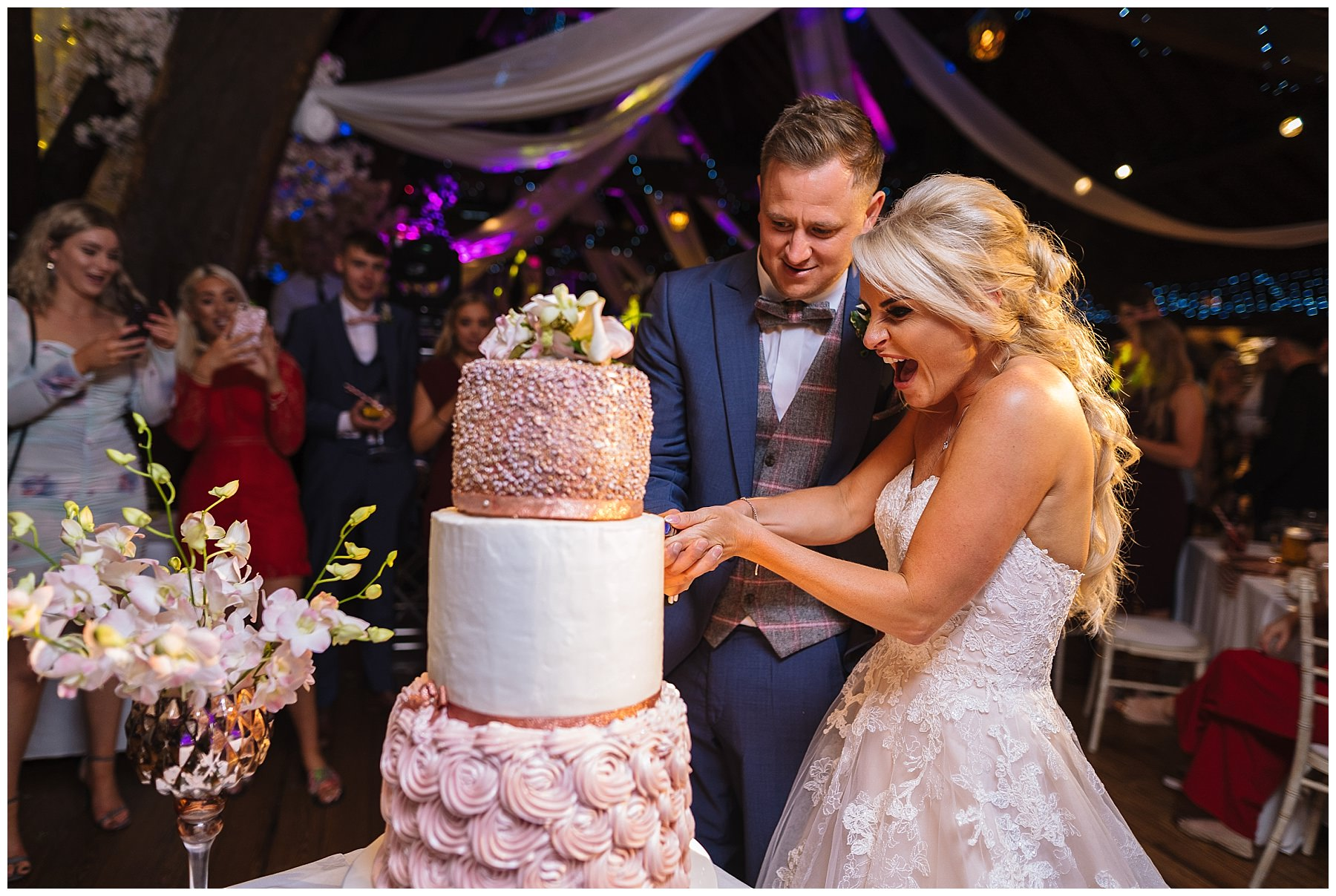 Amazing three tier wedding cake is cut by bride and groom at rivington barn wedding