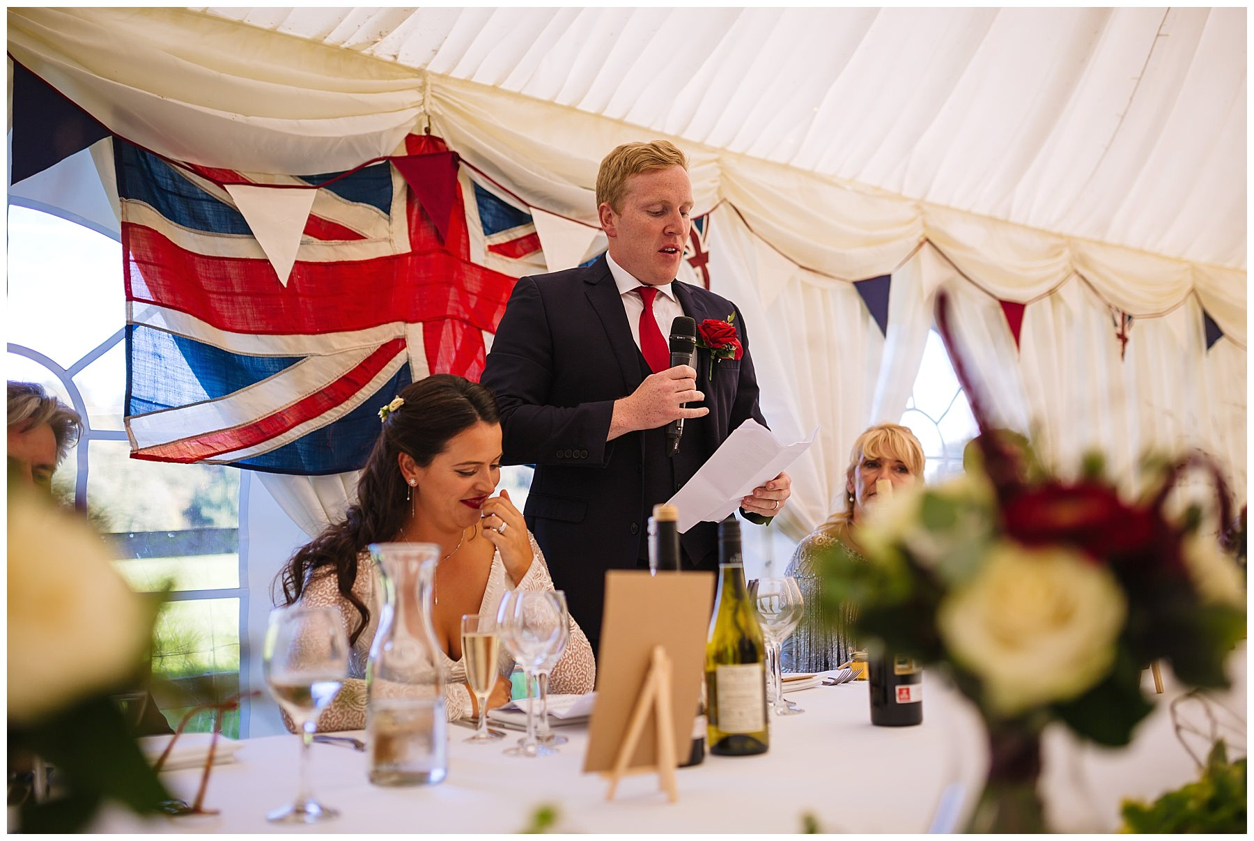 groom stands to address his guests at Hilltop House wedding