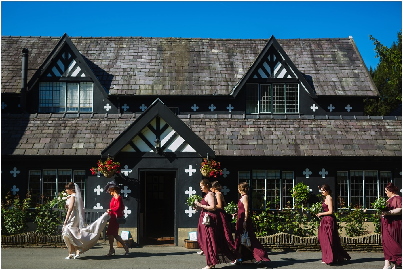 bride and bridesmaids walk to ceremony at samlesbury hall