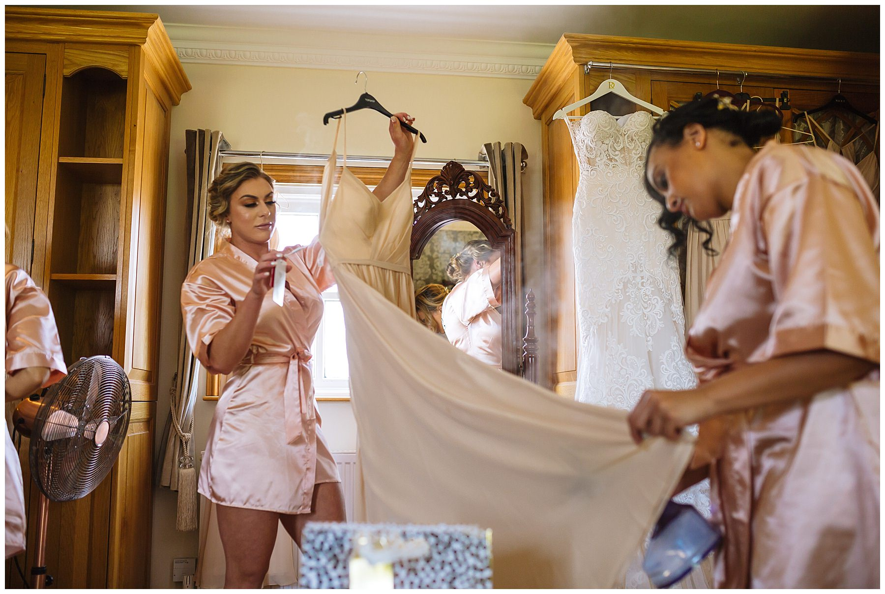 Brides steam dresses during bridal prep