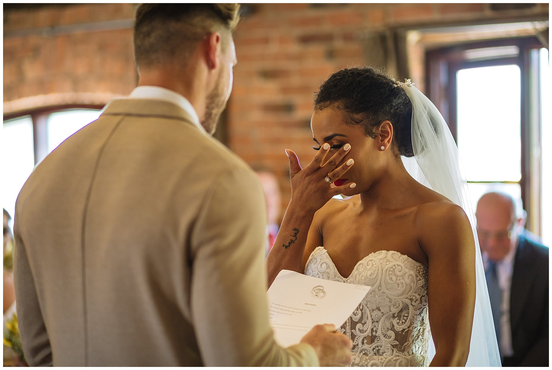 bride wipes away a tear during swancar farm wedding ceremony