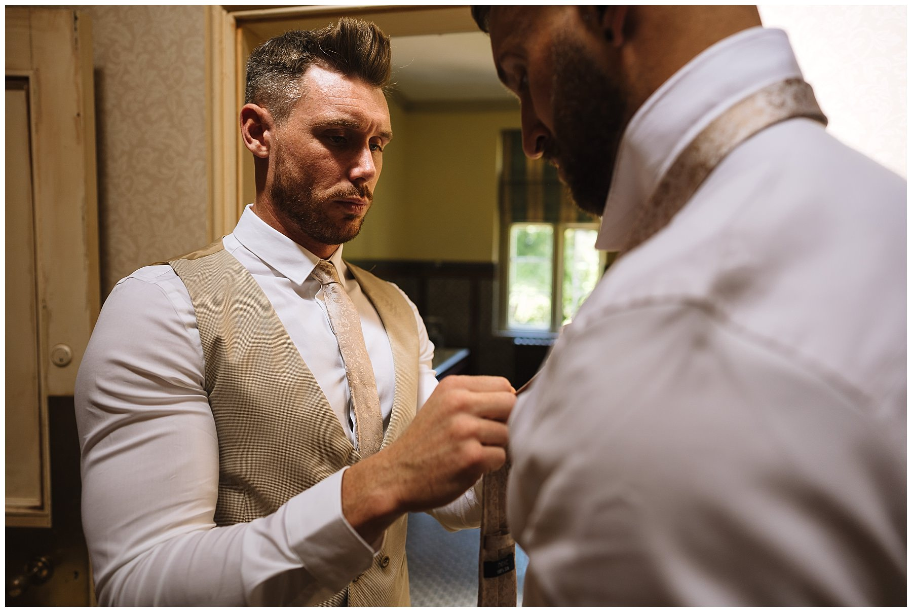 groom helps groomsman fasten his tie