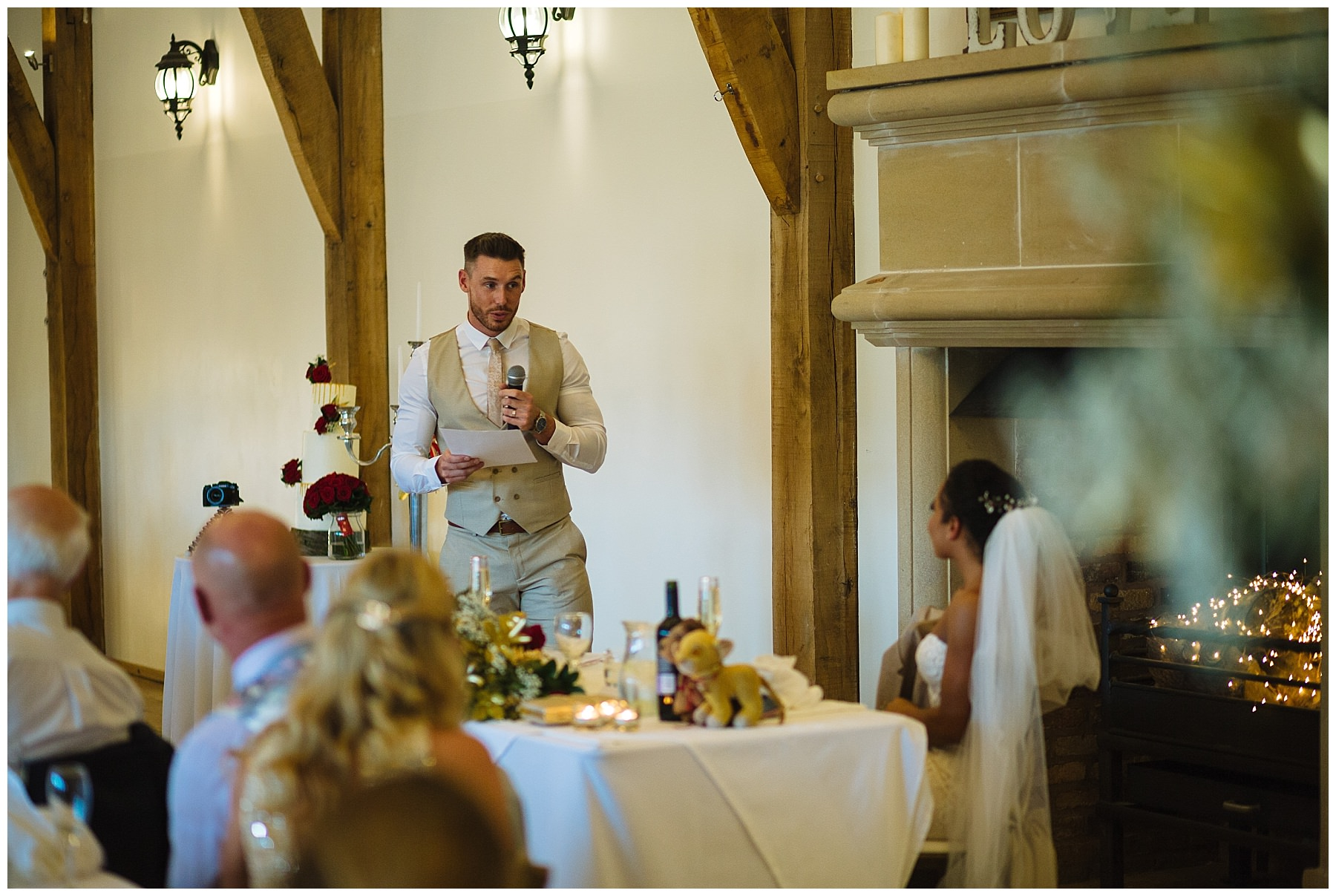 groom stands and speaks to wife during wedding breakfast at swancar farm