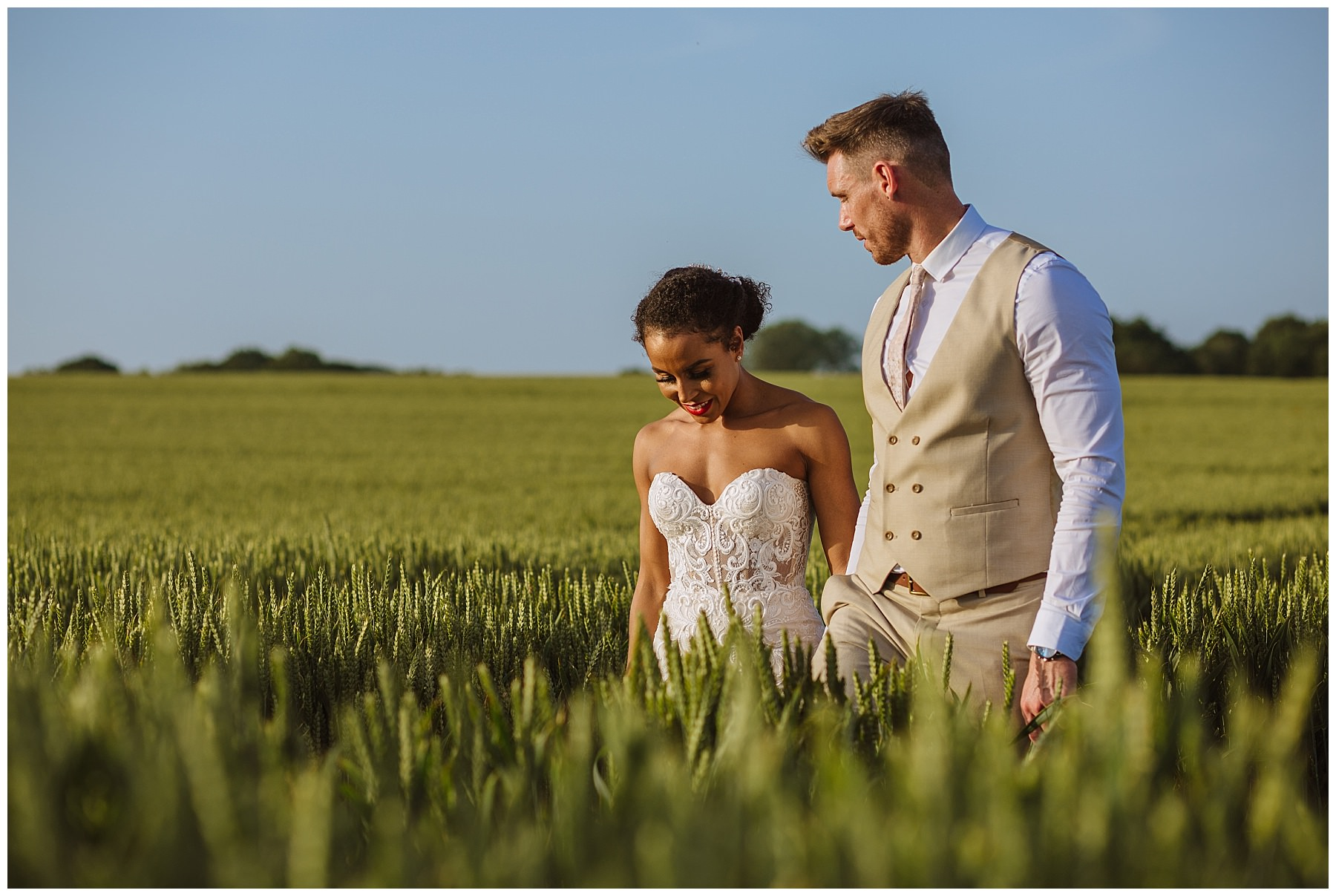 married couple walk through the fields at swancar farm