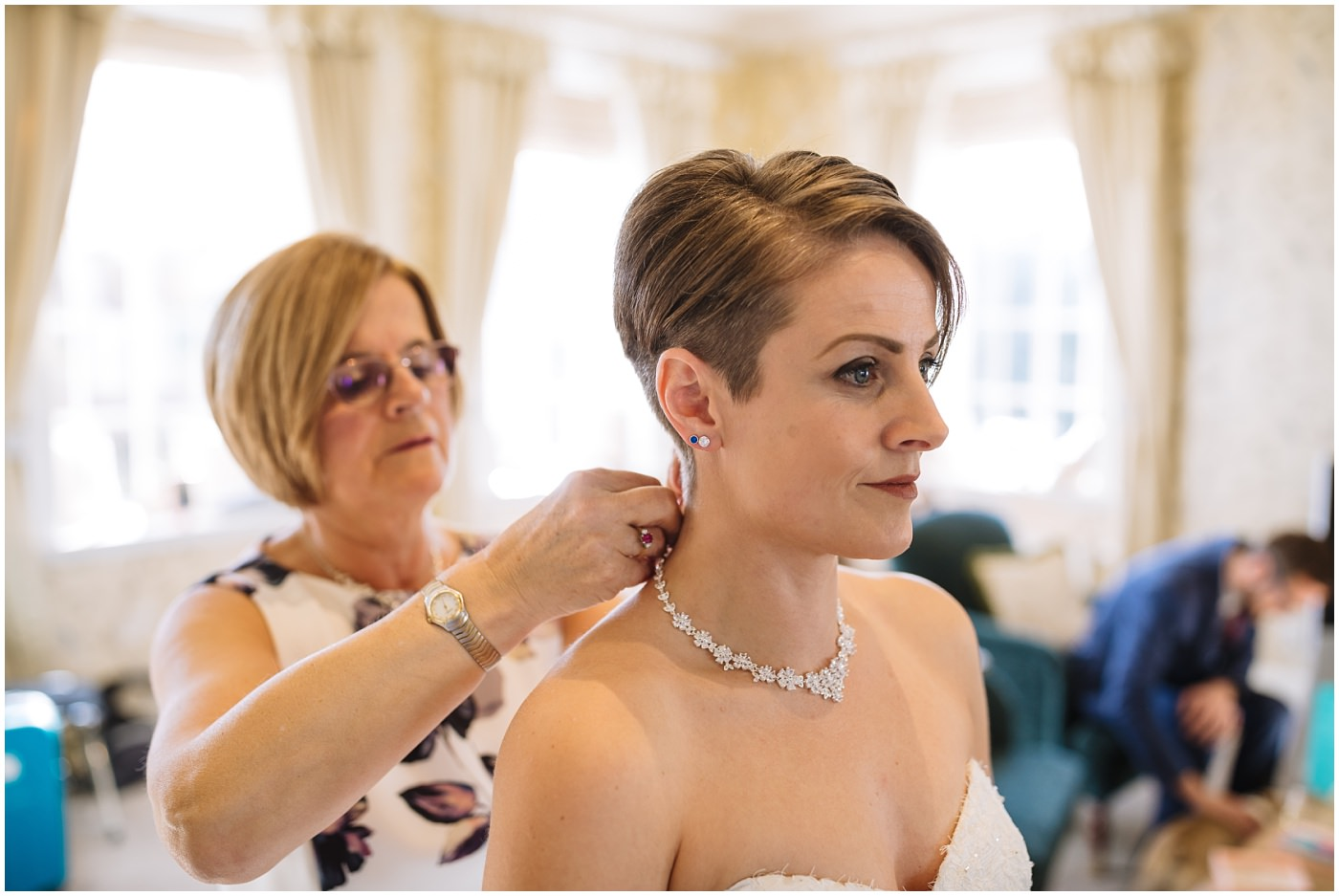 Mother of the bride assists with wedding jewellery