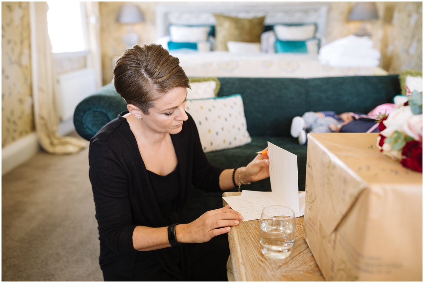 Bride writes a card in bridal suite at eaves hall