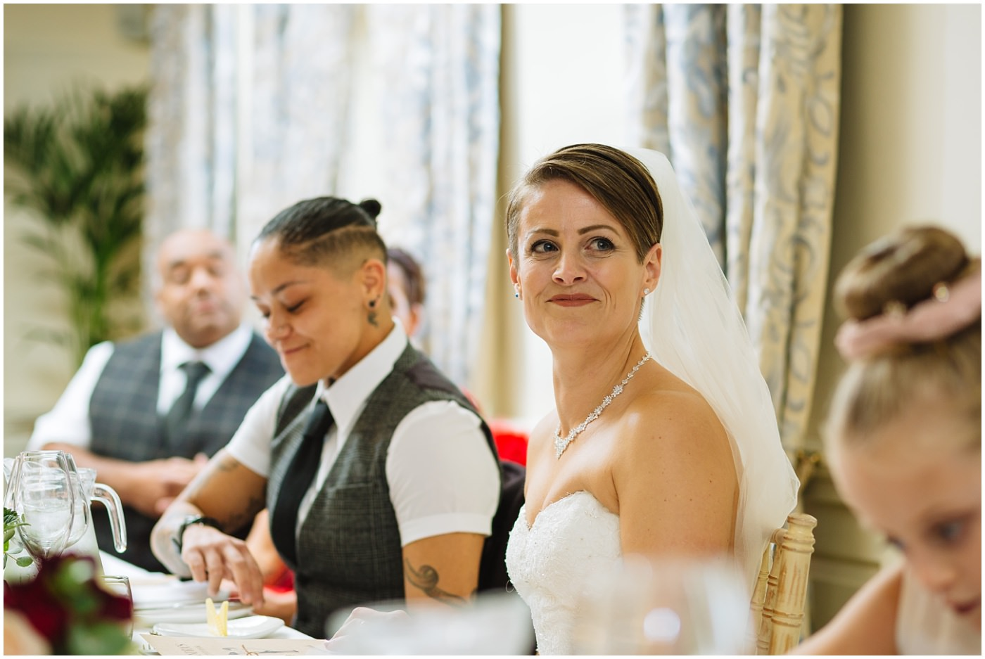 Bride looks on during wedding speeches at eaves hall