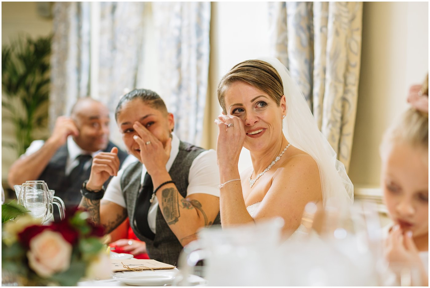 Bride wipes a tear from her eye during Eaves Hall wedding speech
