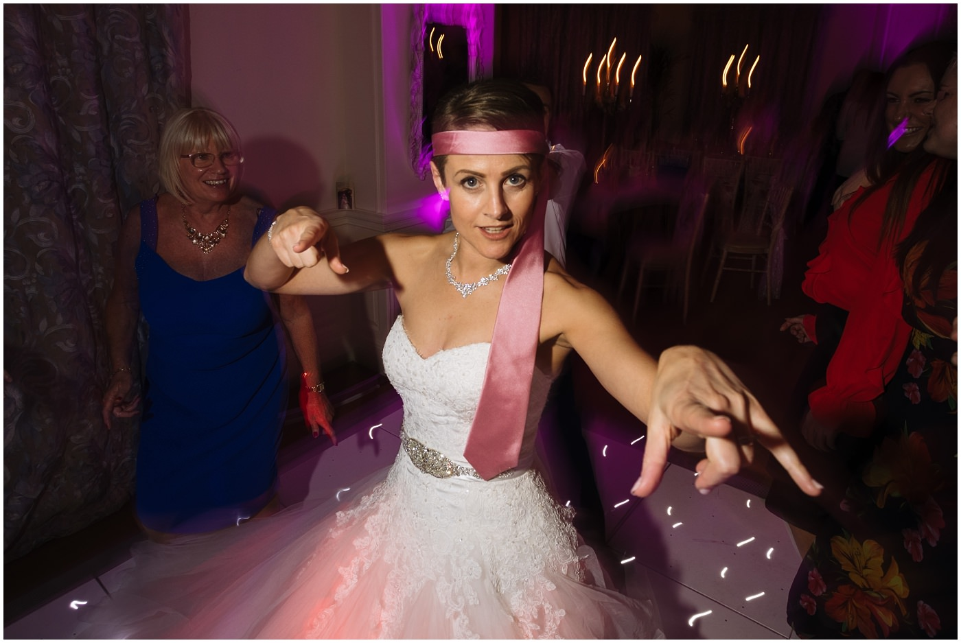 Bride on the dance floor at Eaves hall with Tie around head