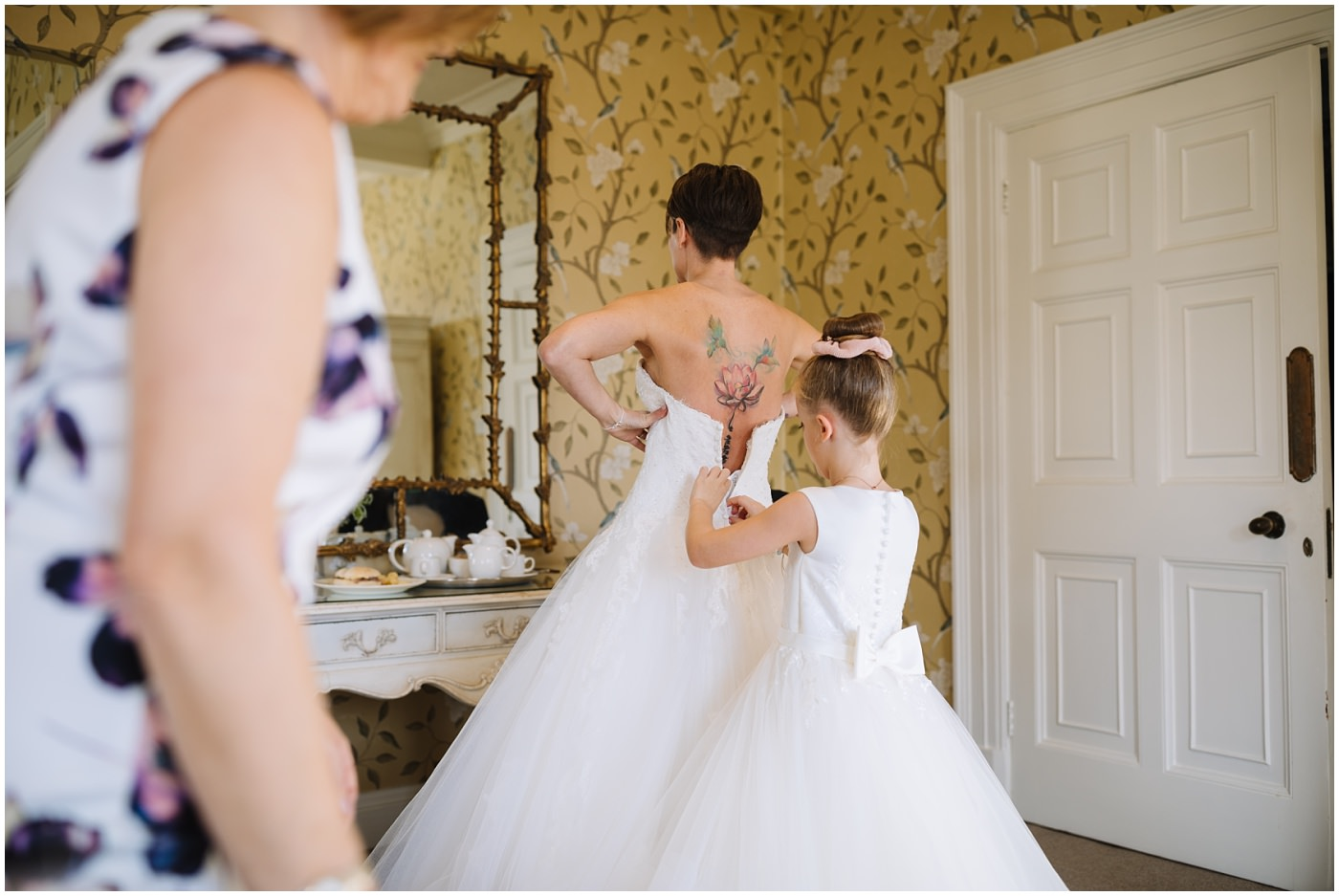 Brides daughter assists with wedding dress at eaves hall