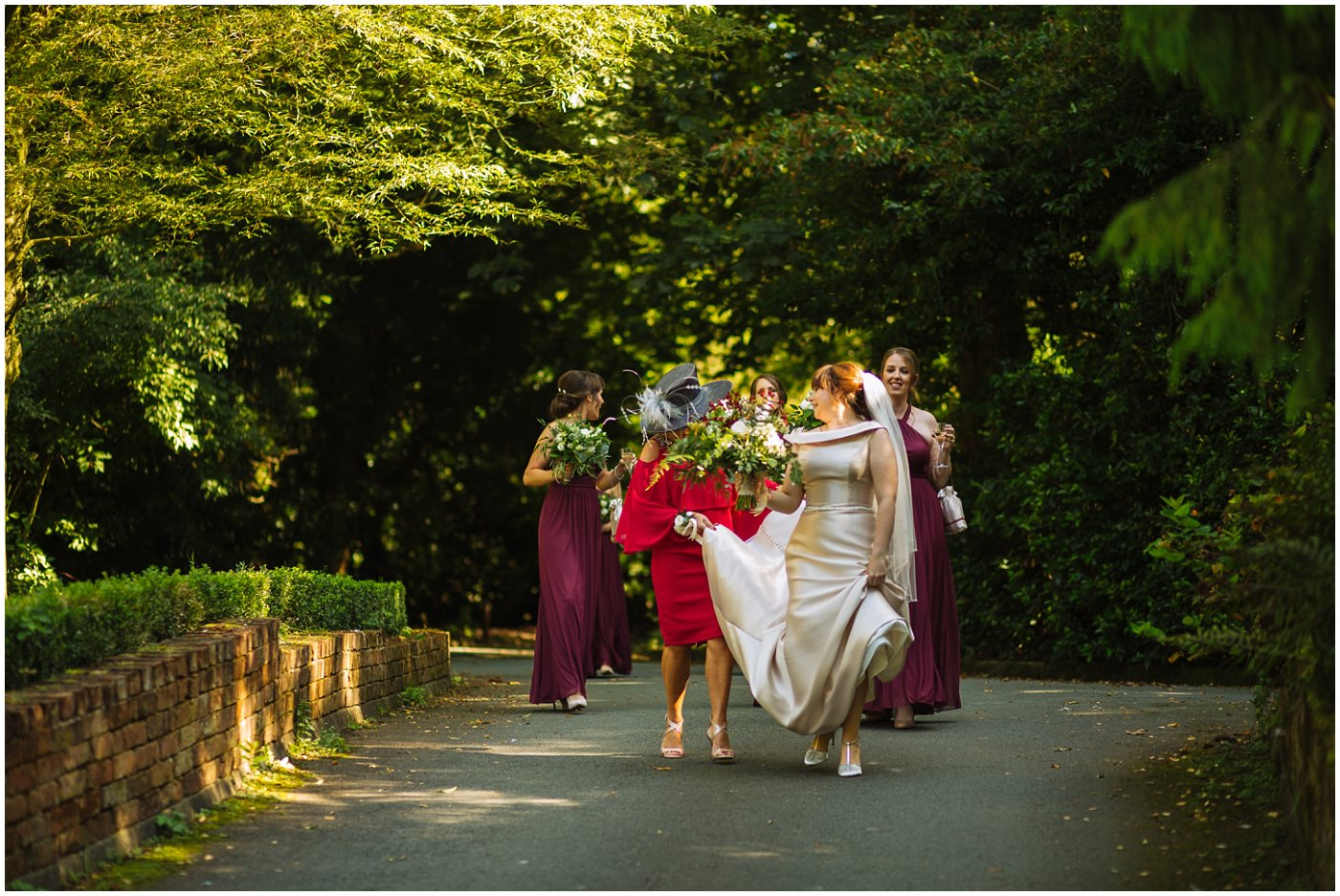 bride and her bridesmaids walk through the grounds of samlesbury hall