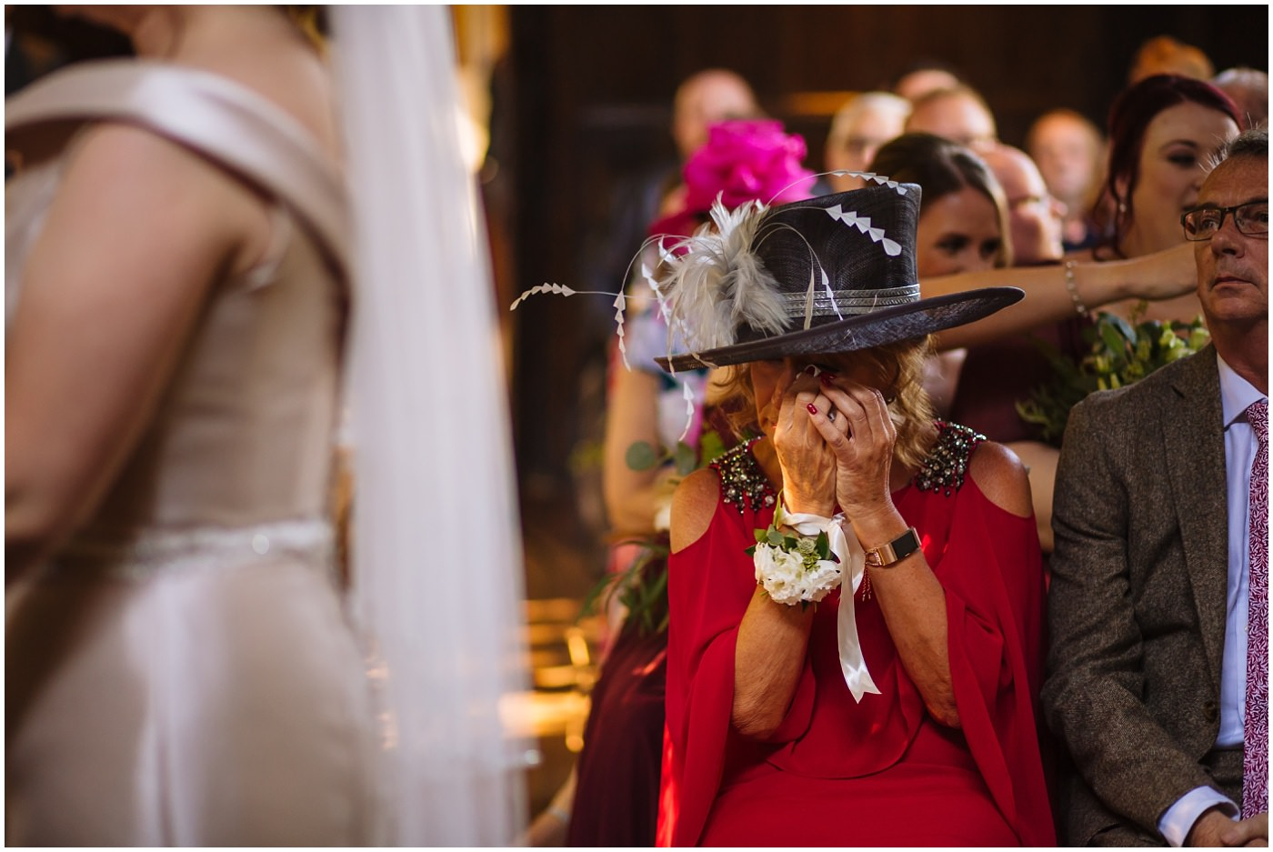 mother of the bride wipes away a tear during emotional samlesbury hall wedding