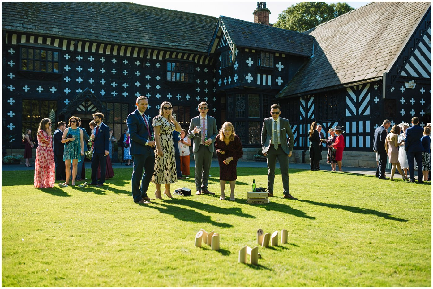 guests enjoy garden games on the lawns at samlesbury hall wedding