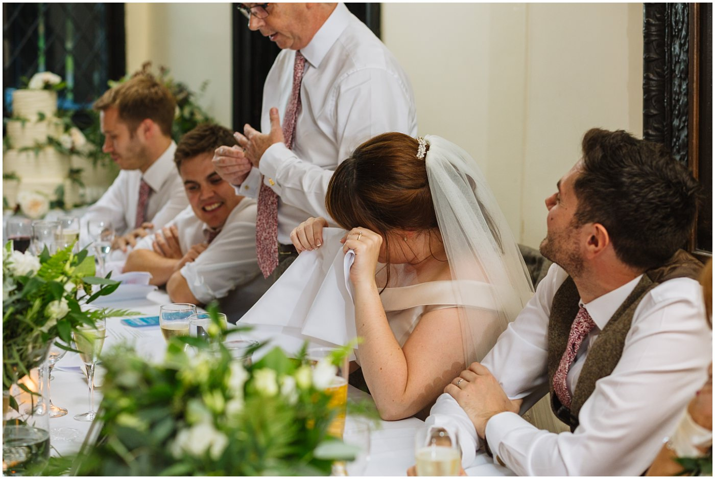 bride wipes a tear from her eye during her dads speech
