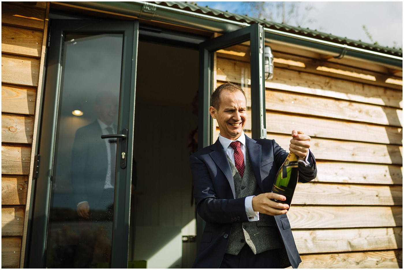 groom opens champagne in front of shepherds hut at sandhole oak barn