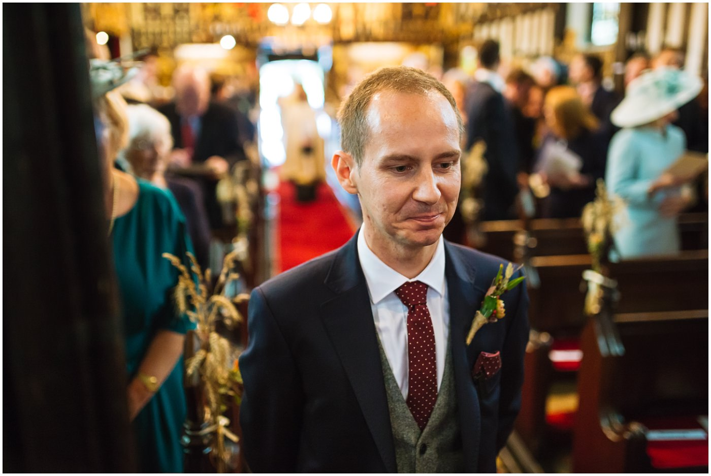 groom stands at the front of church waiting for his bride