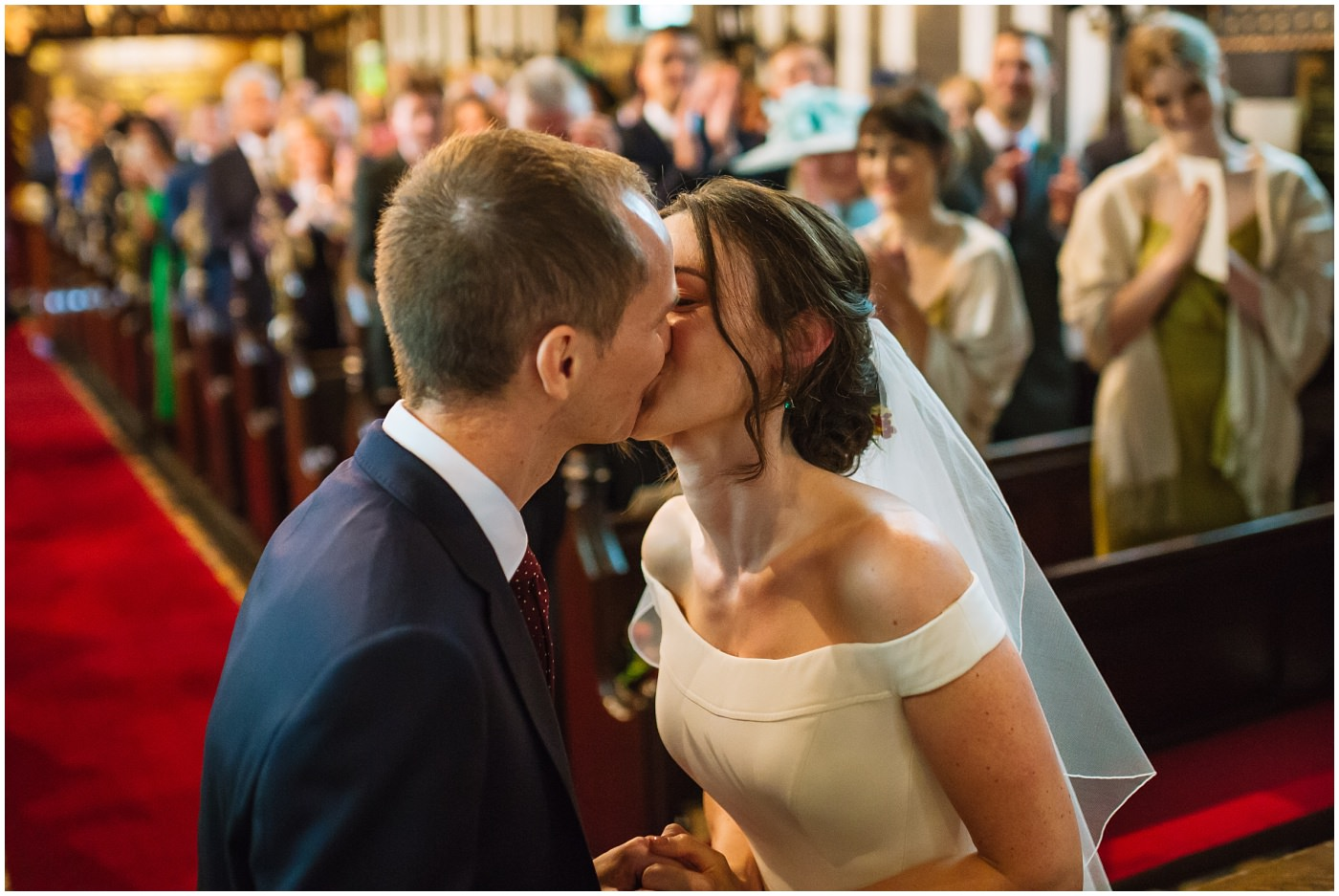 bride and groom kiss during cheshire church ceremony