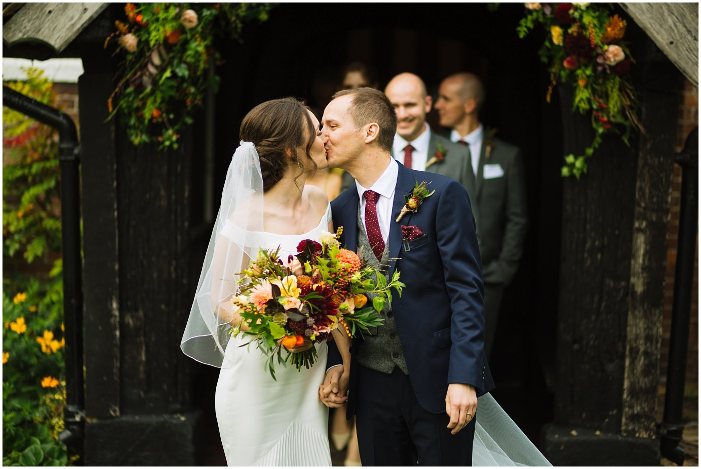 bride and groom kiss as they leave cheshire church wedding