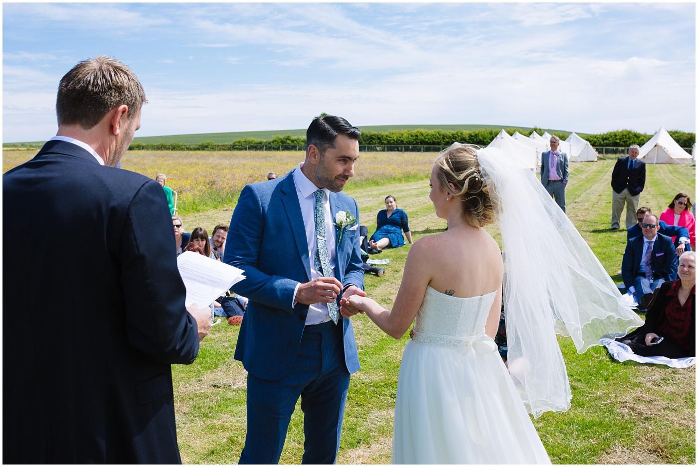 bride and groom exchange rings at wildwood and eden wedding outdoor ceremony