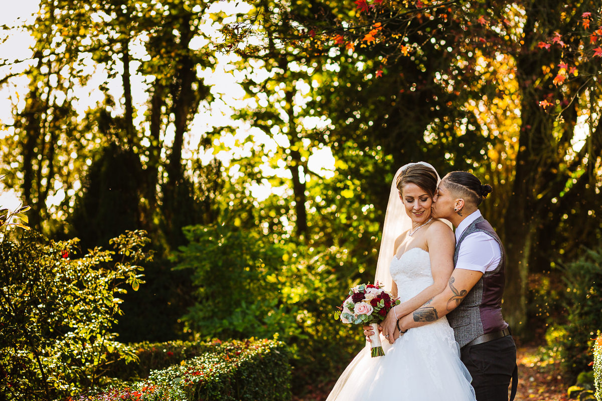 Two brides in the gardens at Eaves Hall on their wedding day
