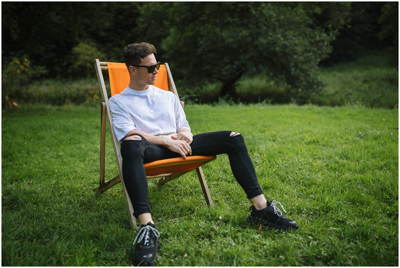 Joel Corry sits in an aperol spritz deck chair at uk's first socially distanced festival